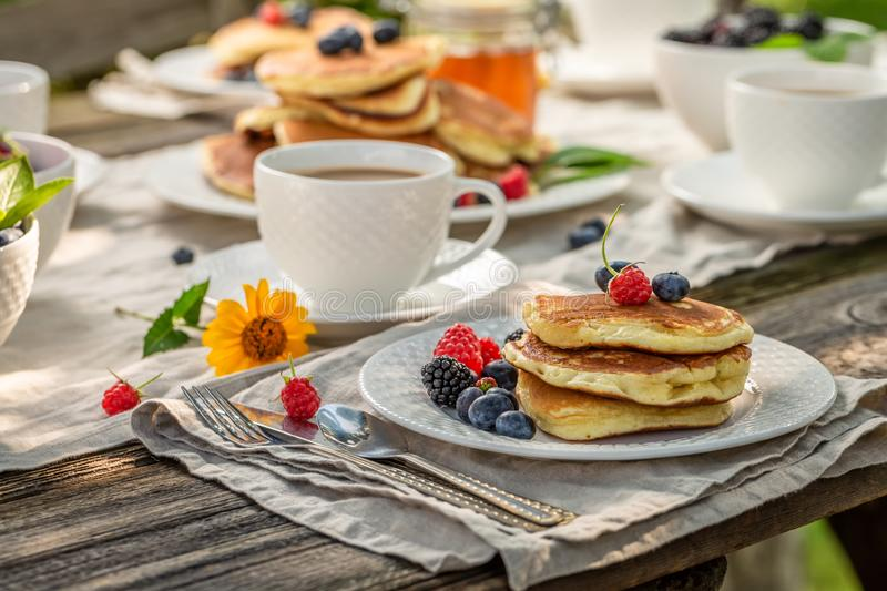 Pancakes with fresh berries and honey in summer garden royalty free stock photo