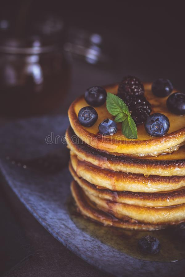Pancakes with Fresh Berries and Maple Syrup on Dark Background royalty free stock photo