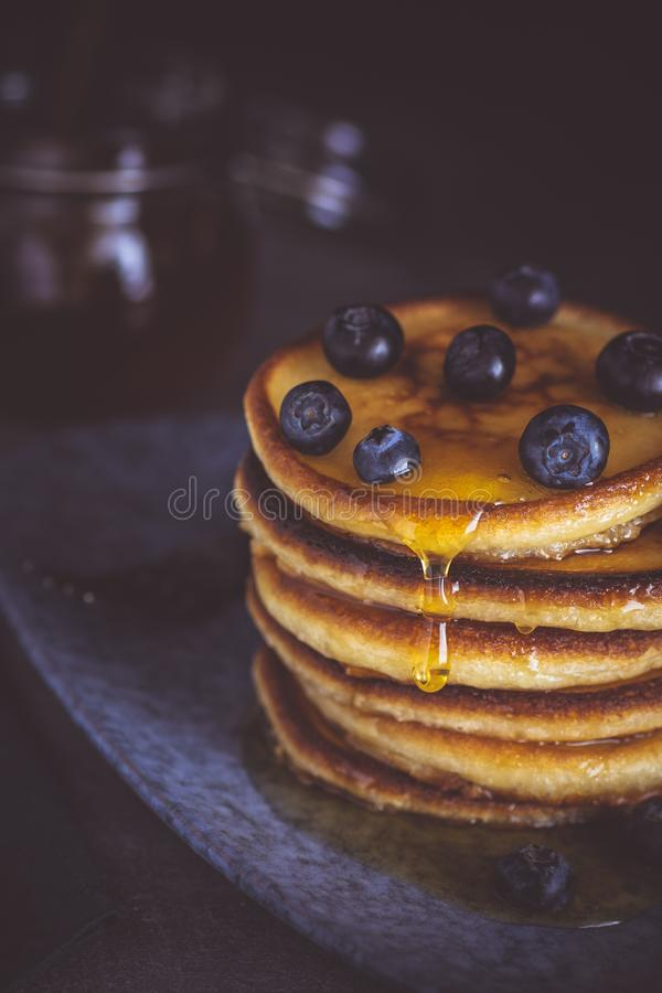 Pancakes with Fresh Berries and Maple Syrup on Dark Background royalty free stock image