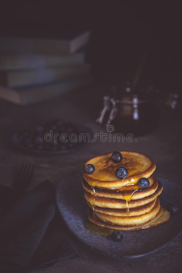 Pancakes with Fresh Berries and Maple Syrup on Dark Background royalty free stock images