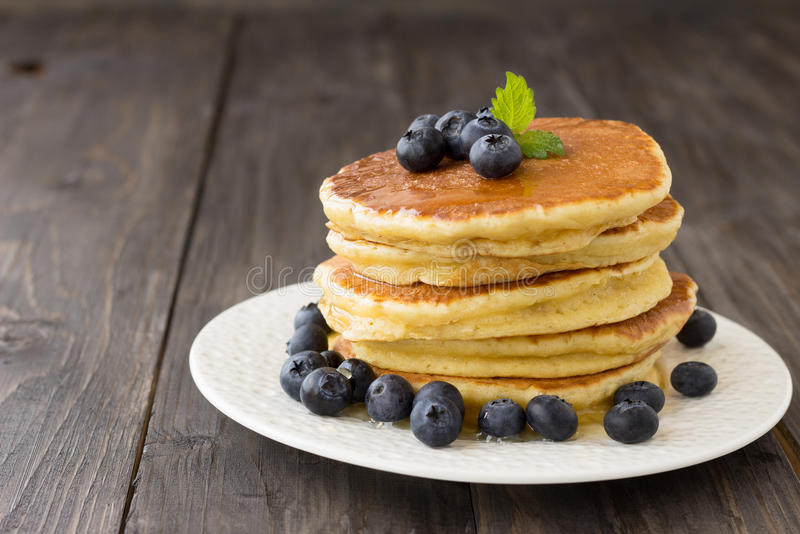 Pancakes with fresh blueberries and honey. On wooden table stock photo