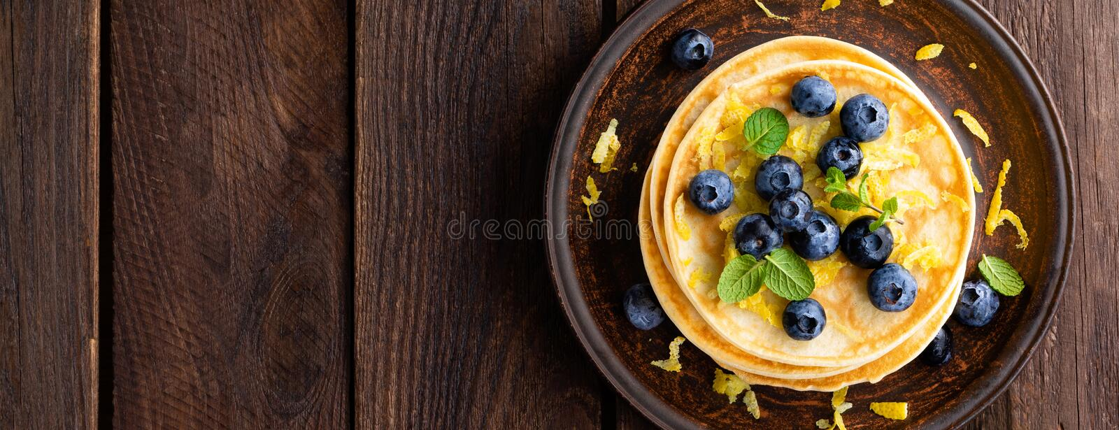 Pancakes with fresh blueberry on wooden rustic background. Top view. Banner. Closeup stock image