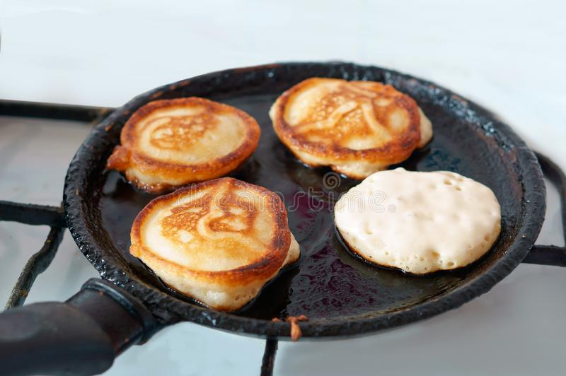 Pancakes are fried in a frying pan, four pancakes are cooked in oil on a frying pan royalty free stock images