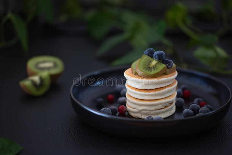 Pancakes with fruits and berries on a black plate stock photos
