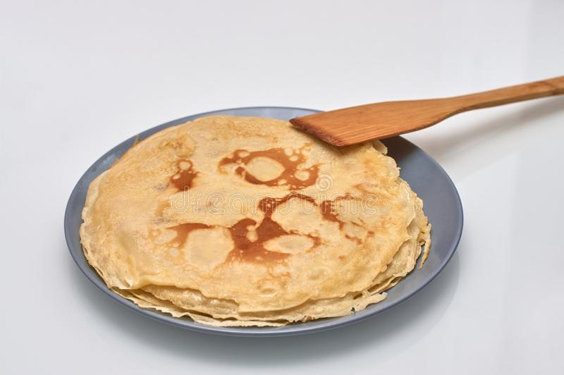 Pancakes on a gray plate and wooden paddle, white background royalty free stock photos