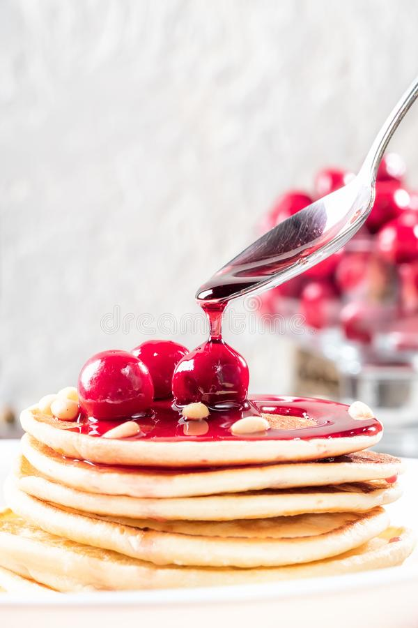 Pancakes homemade cake in stack decorated with berries frozen cherry and pine nut on white plate Sprinkling with cherry. Syrup low key concept healthy breakfast stock photo