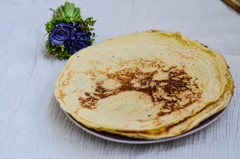 Pancakes. Homemade pancakes and purple flower on whte background stock images