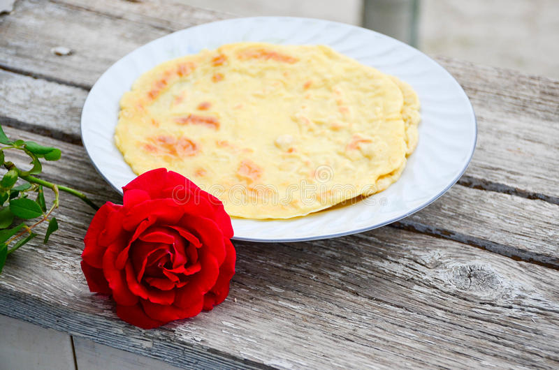 Pancakes. Homemade pancakes and red rose on wooden background royalty free stock photography