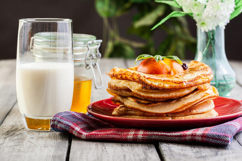 Pancakes with honey, fruit and glass of milk stock photos