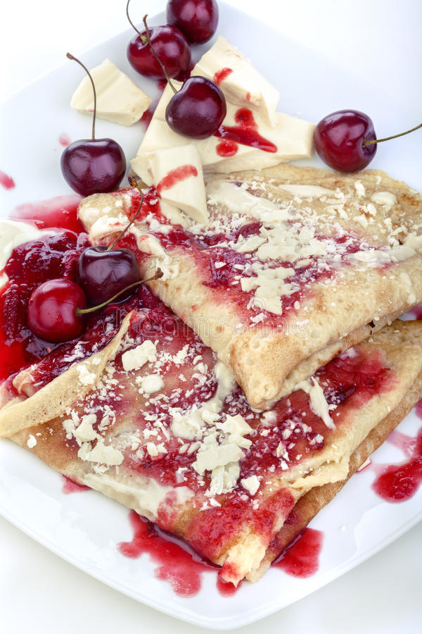 Pancakes. With jam and cherries topped with white chocolate royalty free stock photos