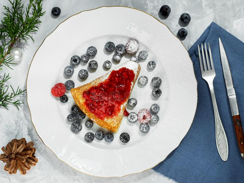 Pancakes with jam are located on a white plate, around the pancakes on a plate are fresh berries. The table is decorated with a stock photography