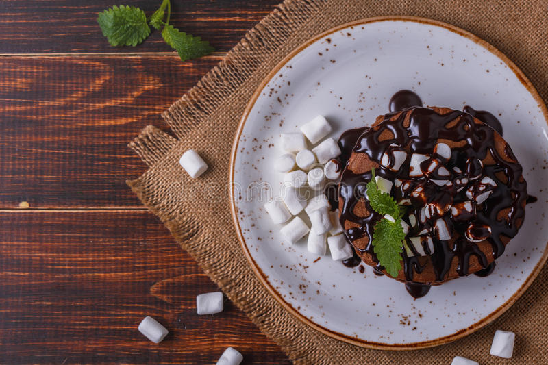 Pancakes with marshmallow and chocolate syrup. Pancakes with marshmallow and chocolate syrup on dark background royalty free stock image