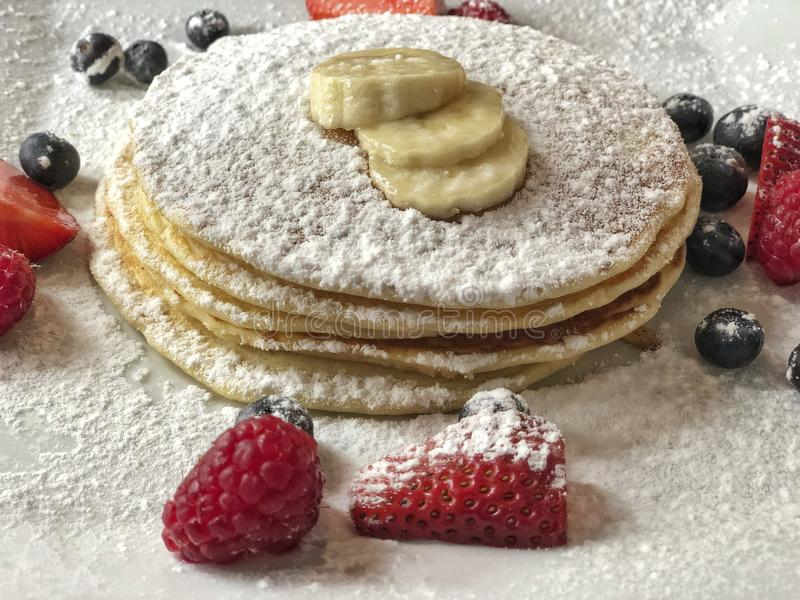 Pancakes on plate decorated with strawberry and banana royalty free stock image