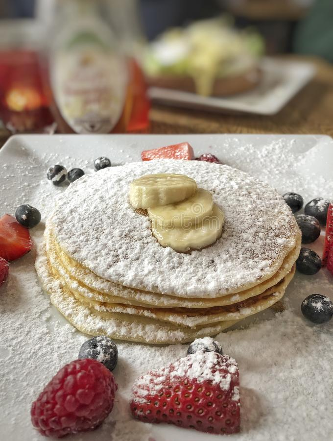 Pancakes on plate decorated with strawberry and banana royalty free stock images