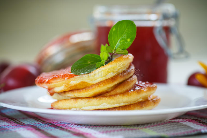 Pancakes with plum jam. On a plate royalty free stock photography