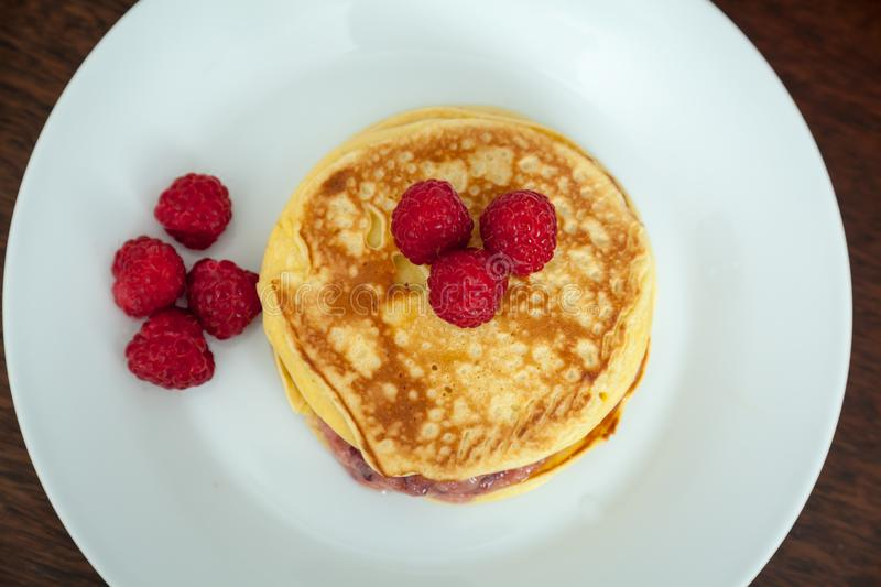 Pancakes with raspberries on the white plate. Top view stock image