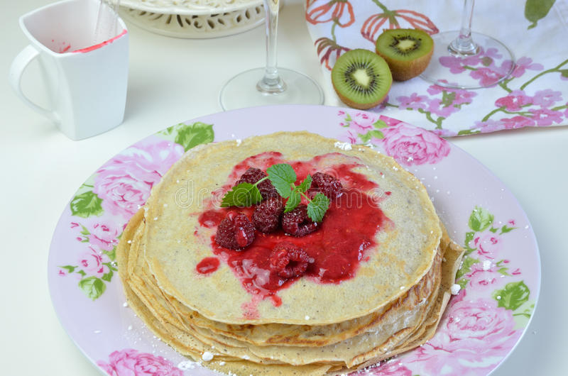 Pancakes with Raspberry Jelly and Lemon Balm. Pile of soft pancakes with natural raspberry jelly and lemon balm on top on floral plate stock image