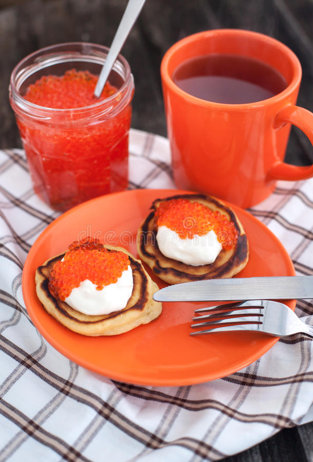 Pancakes with red caviar and sour cream royalty free stock photography