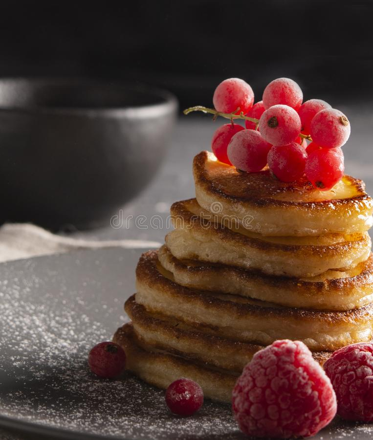 Pancakes with red currant dark powder sugar front stock image