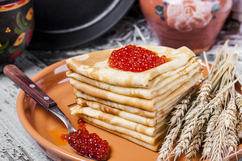 Pancakes with salmon caviar. Traditional Russian meal on wooden background stock images