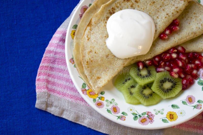 Pancakes with sour cream, kiwi fruit and pomgranate royalty free stock photo