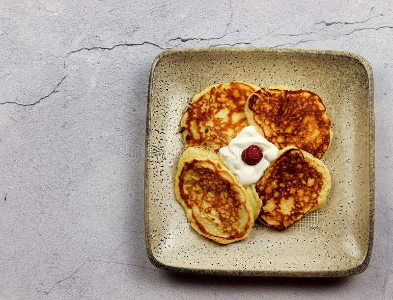 Pancakes with sour cream on a square plate on a light gray background. Top view. Flat lay stock photo
