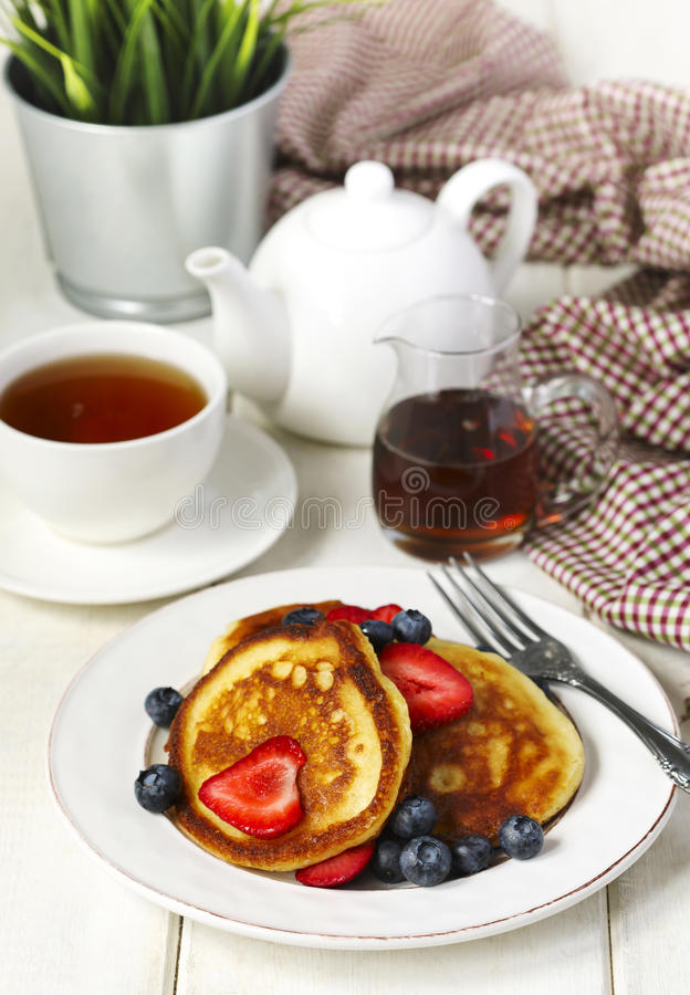 Pancakes with strawberries, blueberries and maple syrup stock image
