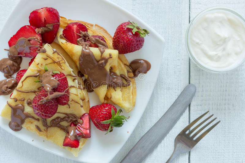 Pancakes with strawberries drizzled with chocolate. On a white wooden background. The view from the top. Photo royalty free stock photography