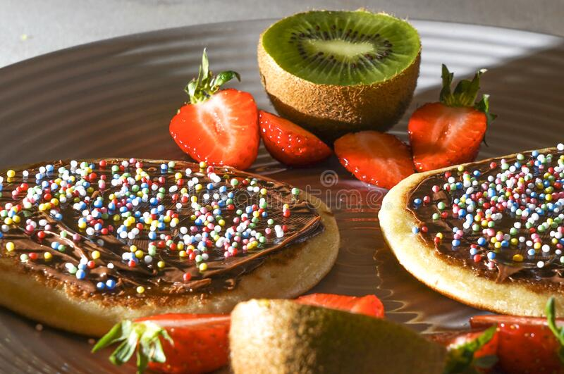 Pancakes with strawberries kiwis and chocolate. Pancakes with chocolate sauce decorated with small multi-color sugar balls on a gray plate with strawberries and stock image