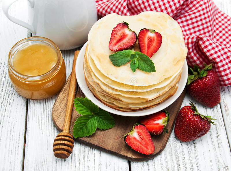 Pancakes with strawberries. Milk and honey on a old wooden table royalty free stock photography