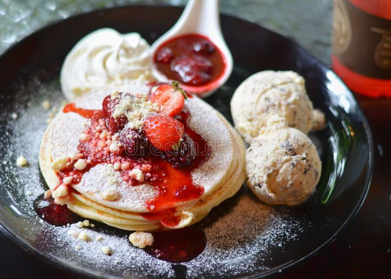 Pancakes with strawberry syrup and icecream. Drlicious royalty free stock images