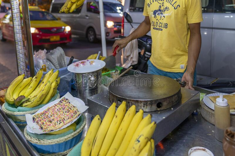 Pancakes on the street, cooking pancakes and street food in unsanitary conditions, spread of coronavirus and infectious diseases. Traditional cooking of street stock image