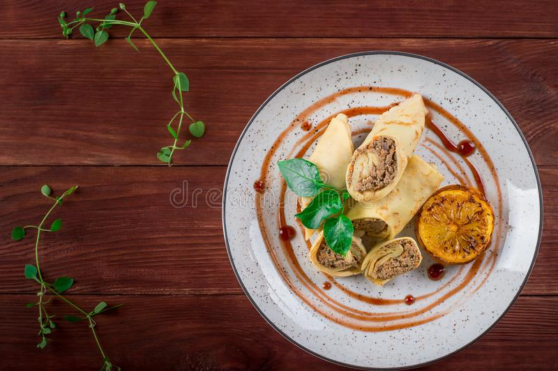 Pancakes stuffed with liver. Wooden rustic background. Top view royalty free stock image