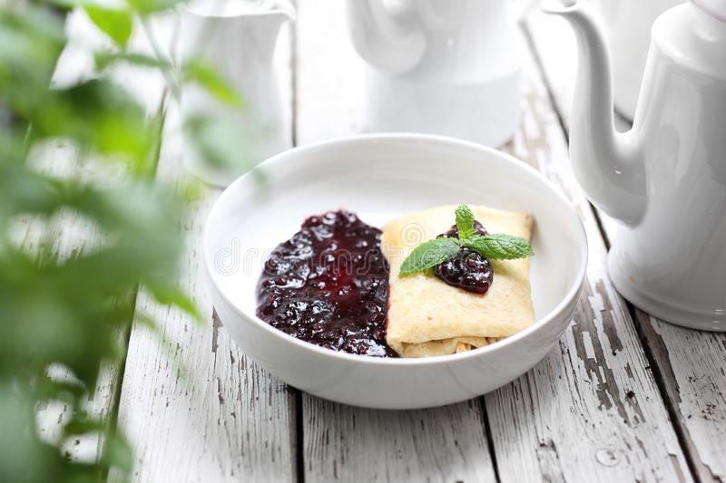 Pancakes stuffed with white cheese with dark fruit jam royalty free stock photo