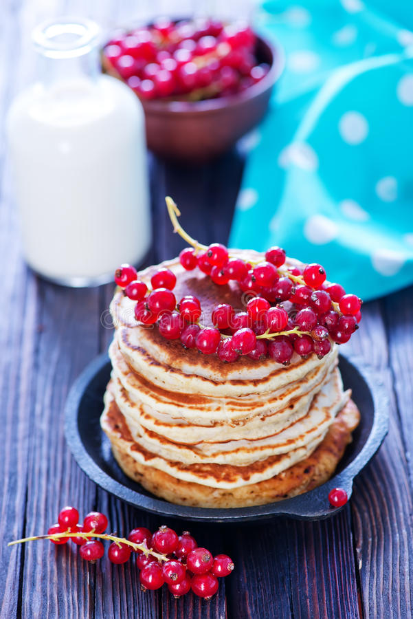 Pancakes. Sweet pancakes with red currant on the plate royalty free stock photos