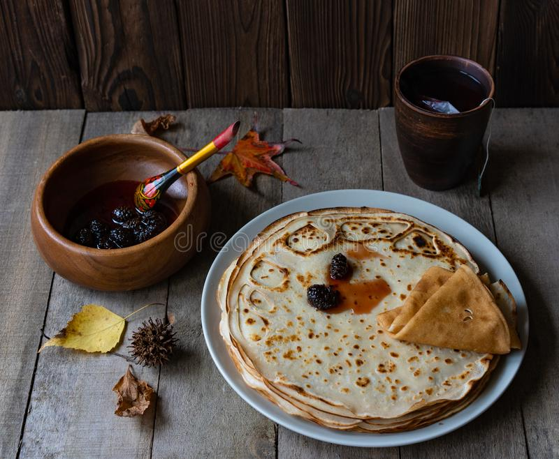 Pancakes, tea and wooden spoon royalty free stock photography