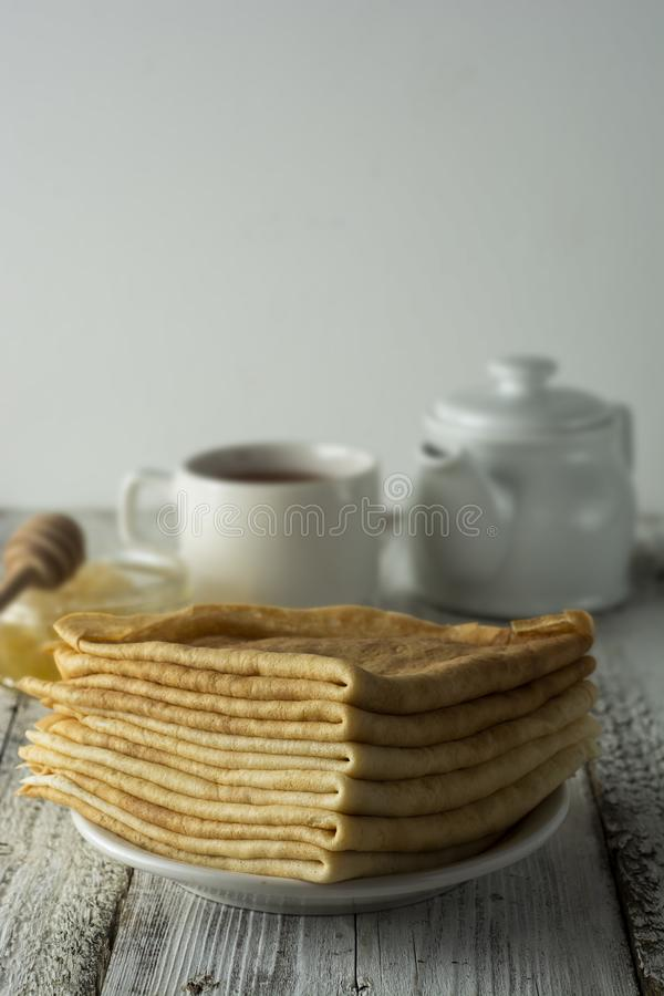 Pancakes. Thin pancakes. Russian bliny. Healthy tasty breakfast - pancakes, a cup of tea and honey. Copy space royalty free stock photography