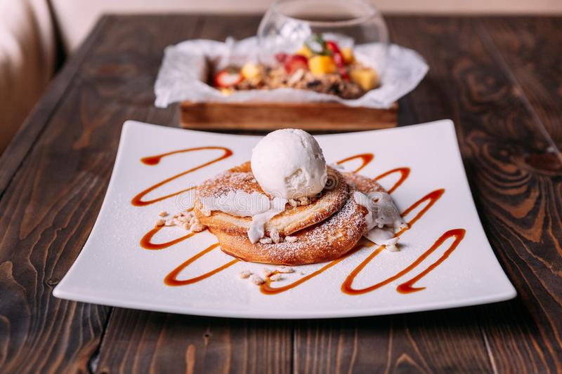 Pancakes topping with a scoop of coconut ice cream, coconut meat, crispy rice and icing over caramel lines on white plate.  royalty free stock photo