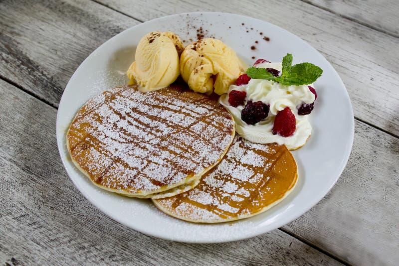 Pancakes with vanila ice cream, whipping cream and icezing royalty free stock photography