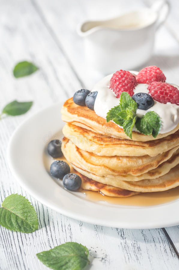 Pancakes with whipped cream and fresh berries stock photo