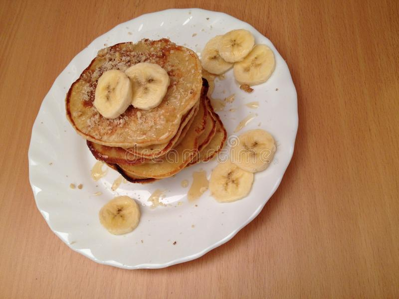 Pancakes on a white plate with banana slices and walnuts stock photography