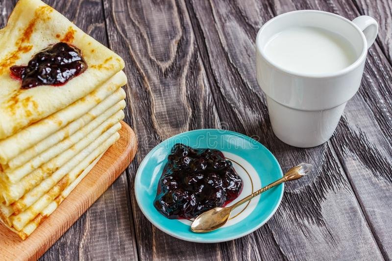 Pancakes on a white plate with honey and a cup of milk. Tasty br royalty free stock images