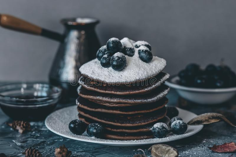 Pancakes on a white plate in powdered sugar with grapes on a gray background. royalty free stock photography