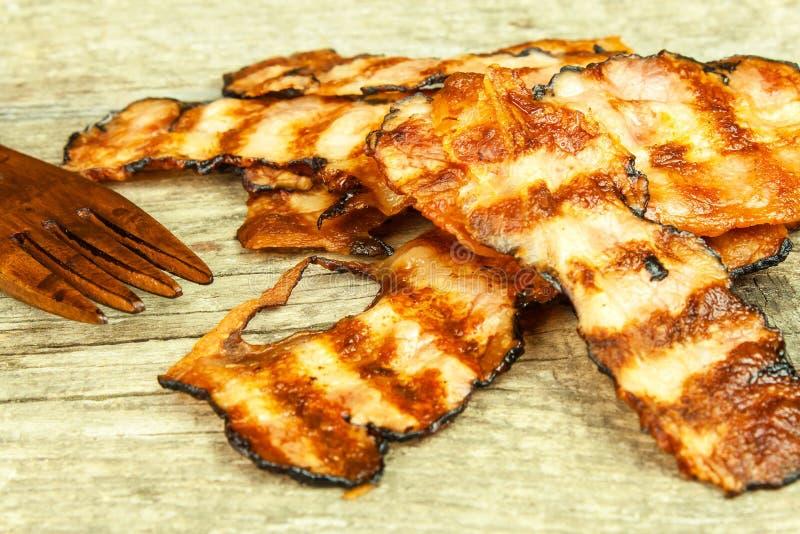Pancetta affumicata cotta Bacon cucinato croccante sulla Tabella Alimento non sano Rischio di obesità Barbecue casalingo immagini stock