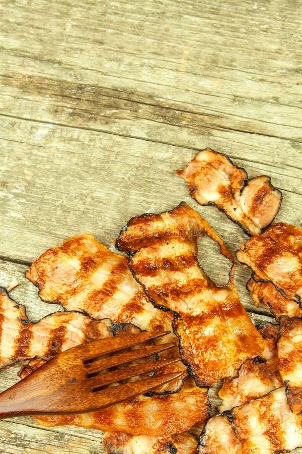 Pancetta affumicata cotta Bacon cucinato croccante sulla Tabella Alimento non sano Rischio di obesità Barbecue casalingo immagini stock libere da diritti