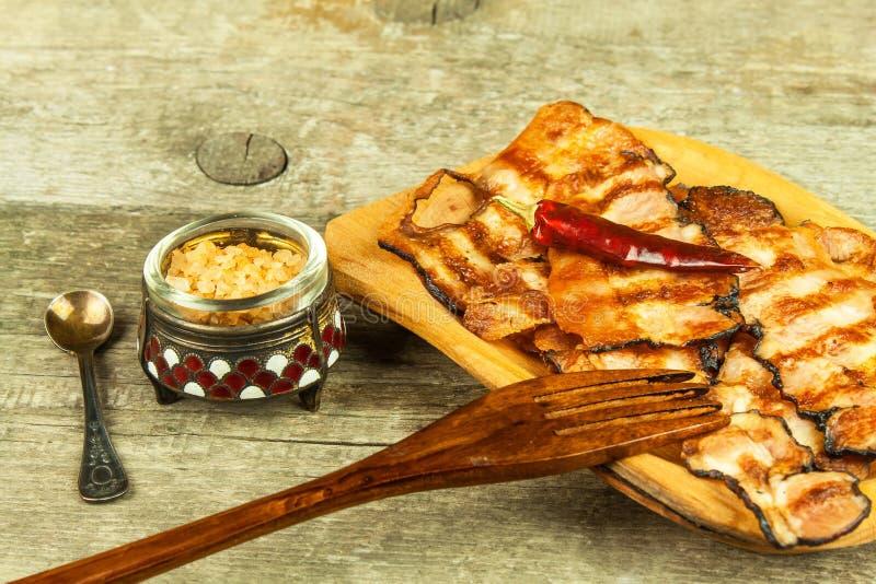 Pancetta affumicata cotta Bacon cucinato croccante sulla Tabella Alimento non sano Rischio di obesità Barbecue casalingo immagine stock