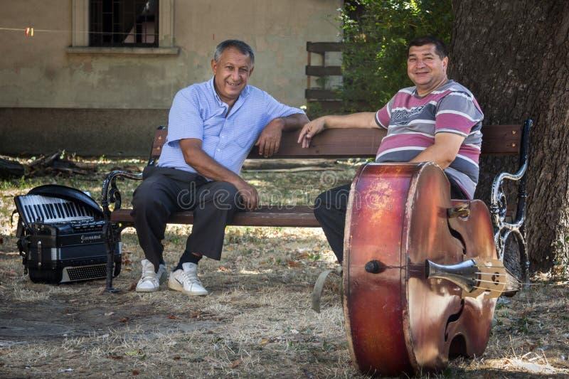 PANCEVO, СЕРБИЯ - 1-ОЕ АВГУСТА 2015: 2 сербских музыканта одно accordeonist, одно contrabassist имея пролом перед представлением стоковые фото