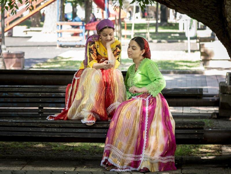PANCEVO, SÉRVIA - 23 DE MAIO DE 2015: Meninas de Roma que olham seus smartphones no quadrado principal do ` s de Pancevo imagem de stock