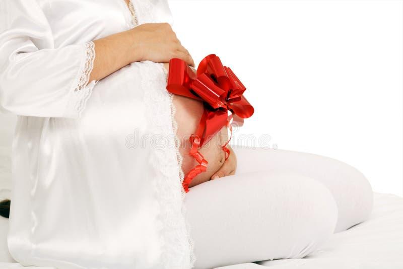 Pancia della donna incinta con il fiore fotografia stock libera da diritti