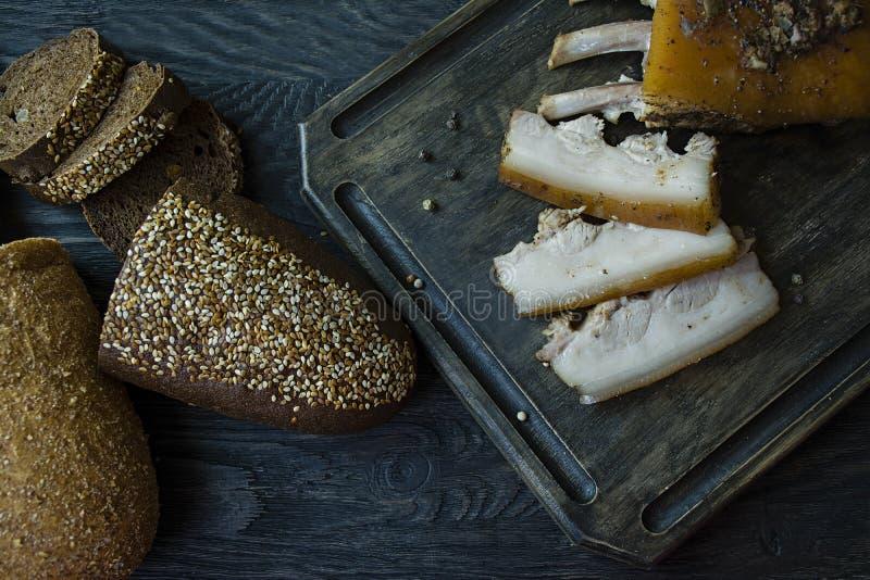 Pancia di carne di maiale cotta con le spezie, pane fresco Grasso ucraino Piatto tradizionale dell'Ucraina Priorit? bassa di legn fotografia stock